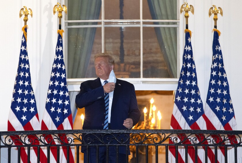 President Trump takes off his mask on a White House balcony after returning from being treated for COVID-19.