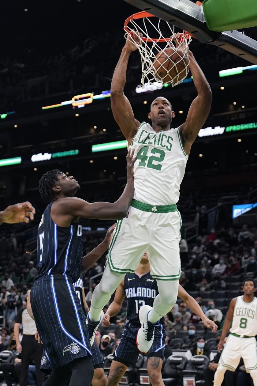 Boston Celtics center Al Horford (42) slams a dunk against Orlando Magic center Mo Bamba, left, during the first half of an NBA preseason basketball game, Monday, Oct. 4, 2021, in Boston. (AP Photo/Charles Krupa)