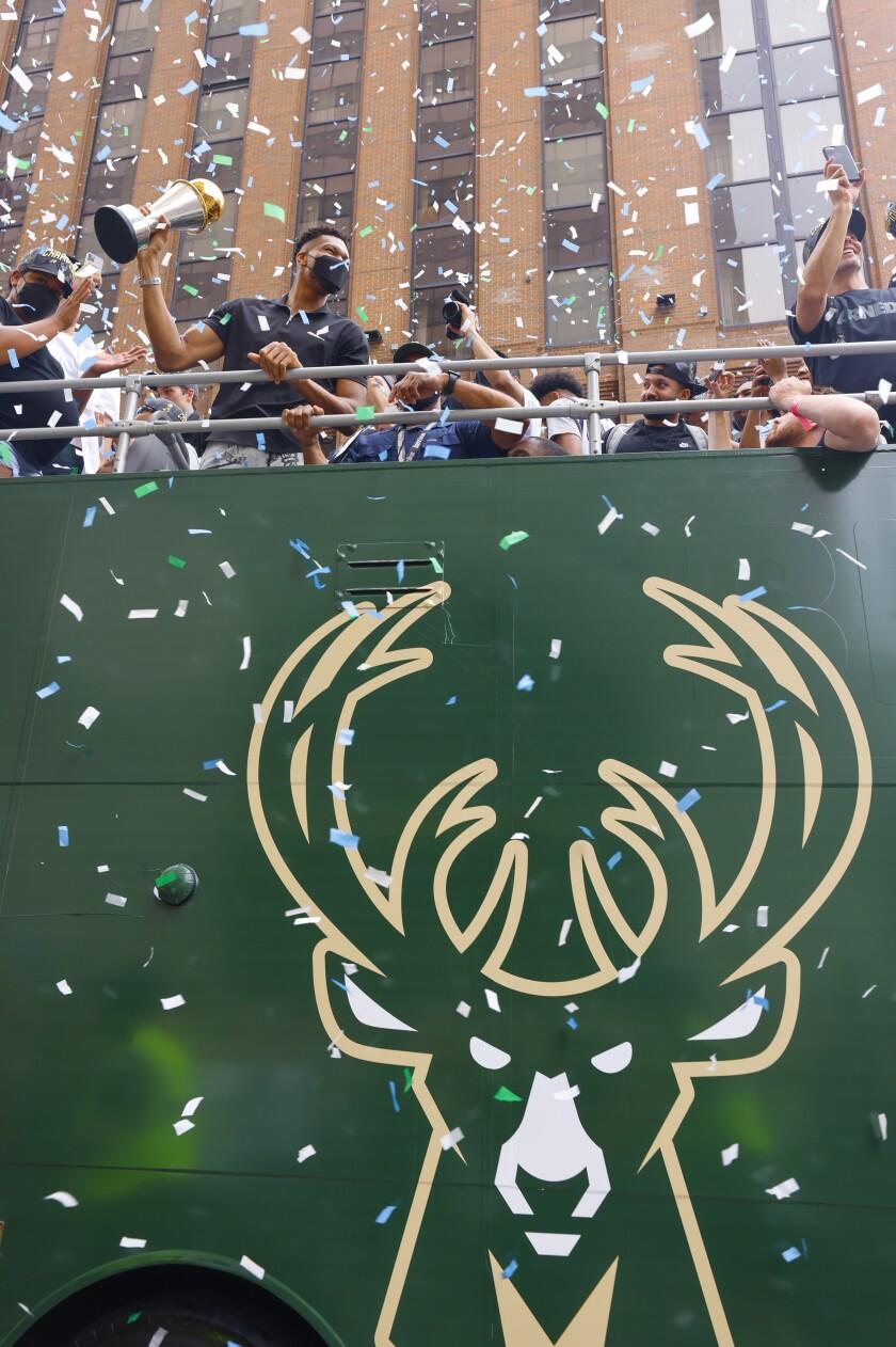 Milwaukee Bucks' Giannis Antetokounmpo holds up the MVP trophy during a parade for the NBA Champion Milwaukee Bucks basketball team Thursday, July 22, 2021, in Milwaukee. (AP Photo/Jeffrey Phelps)