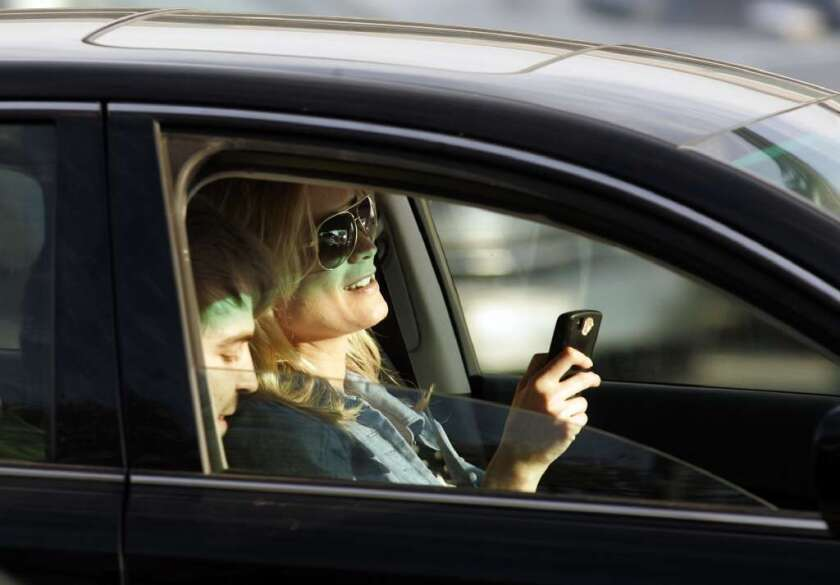 This driver is using her cellphone while trying to focus on the road ahead. A new study quantifies the risk of this and other types of distracted driving.