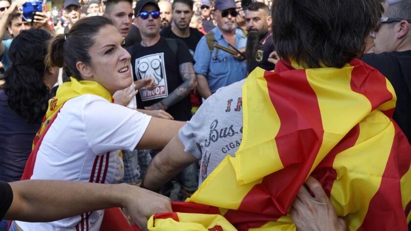 A woman wearing a Spanish flag hits a man wearing an Independence flag, followinga demonstration eru