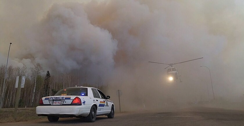 Royal Canadian Mounted Police officers carry out rescue and evacuation work near Fort McMurray.