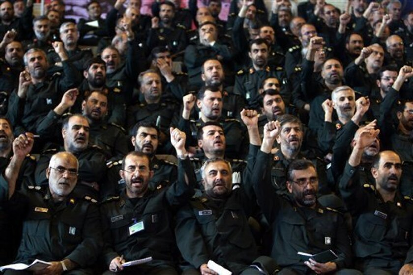 FILE- In this Sept. 11, 2007 file photo, Iranian Revolutionary Guard commanders chant slogans during their meeting with President Mahmoud Ahmadinejad, not pictured, in Tehran, Iran. Iran's powerful Revolutionary Guard is now in the cross-hairs of U.N. sanctions, but it also represents an elusive target that is highly skilled in tactics used for decades by Tehran to bypass economic roadblocks, analysts and experts say. (AP Photo/ISNA, Rouhollah Vahdati)