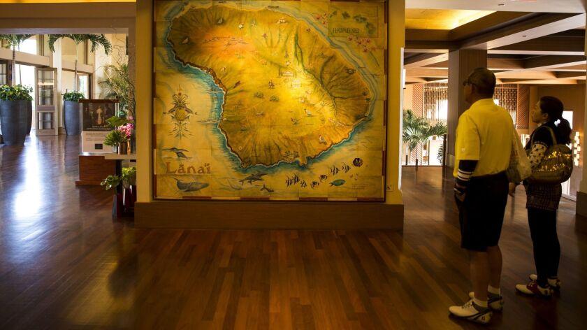 LANAI CITY, HI - APRIL 03: Visitors look at a map of the the Hawaiian island of Lanai in the lobby o