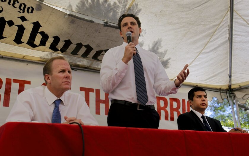 San Diego City Council members and mayoral candidates Kevin Faulconer, left, and David Alvarez, right, along with former Assemblyman Nathan Fletcher, center, debate at the Logan Heights Family Health Center last September.