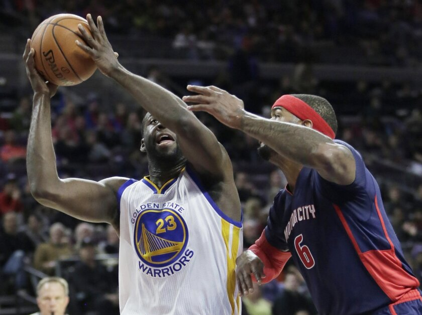 Golden State Warriors' Draymond Green (23) tries to take a shot against Detroit Pistons' Josh Smith (6) during the first half of an NBA basketball game Sunday, Nov. 30, 2014, in Auburn Hills, Mich. (AP Photo/Duane Burleson)