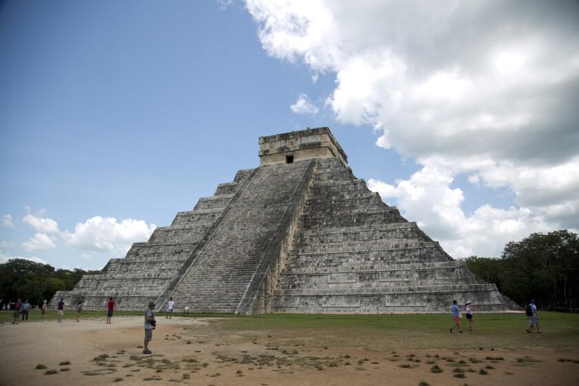 Algunos turistas caminan en las ruinas mayas de Chichén Itzá