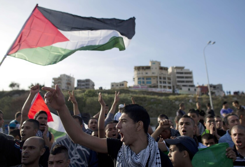 Israeli Arabs in Umm al-Faham hold Palestinian flags shouting slogans during a protest last week against an act of vandalism at the city's mosque.