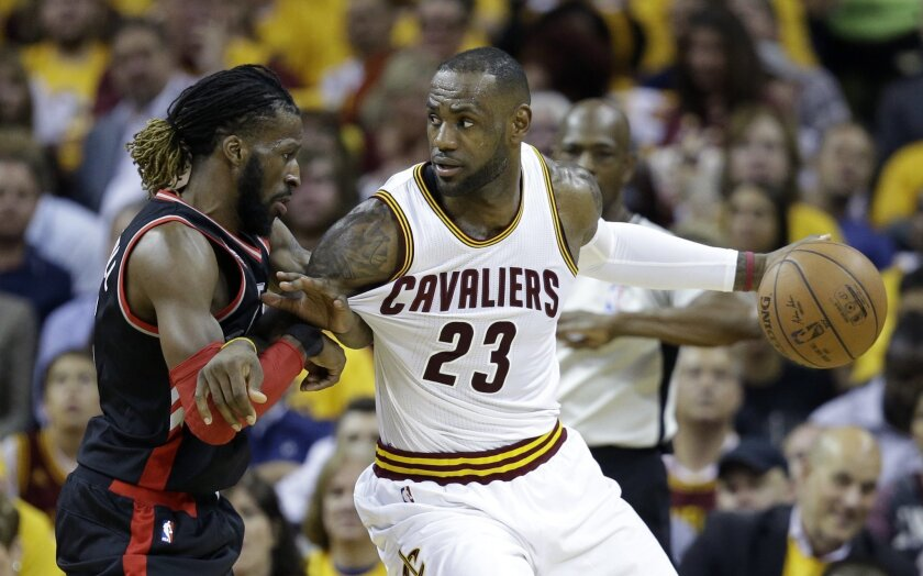 Cleveland Cavaliers' LeBron James (23) looks to pass around Toronto Raptors' DeMarre Carroll (5) during the first half of Game 5 of the NBA basketball Eastern Conference finals Wednesday, May 25, 2016, in Cleveland. (AP Photo/Tony Dejak)
