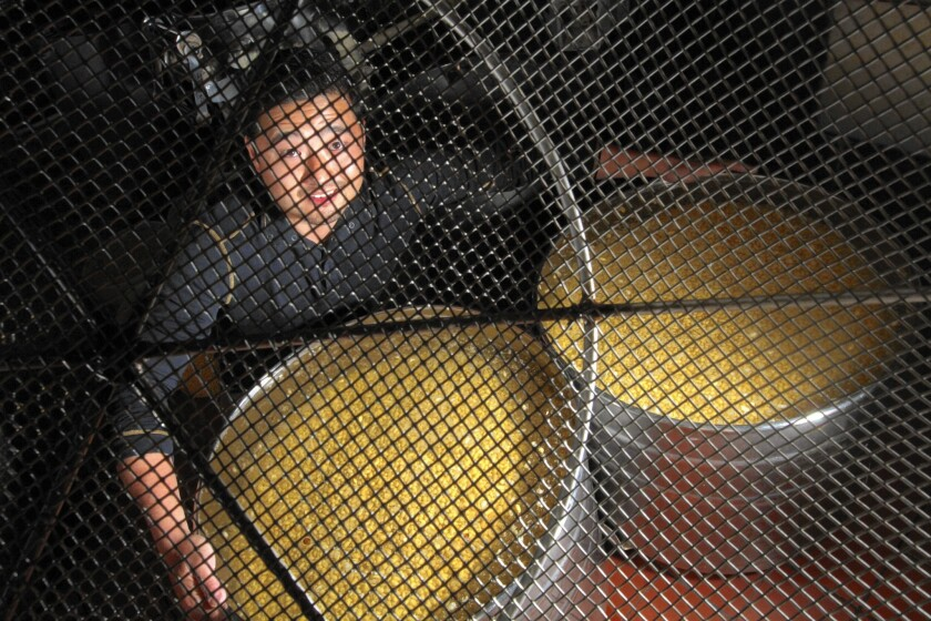 Koki Sato with tubs of soybeans soaking in water that will be used to make tofu at Gardena-based Meiji Tofu.