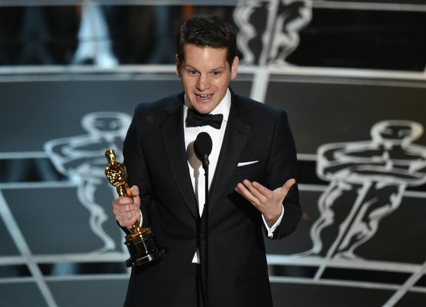 """Graham Moore accepts the award for the best adapted screenplay for """"The Imitation Game"""" at the Oscars on Sunday, Feb. 22, 2015, at the Dolby Theatre in Los Angeles. (Photo by John Shearer/Invision/AP)"""