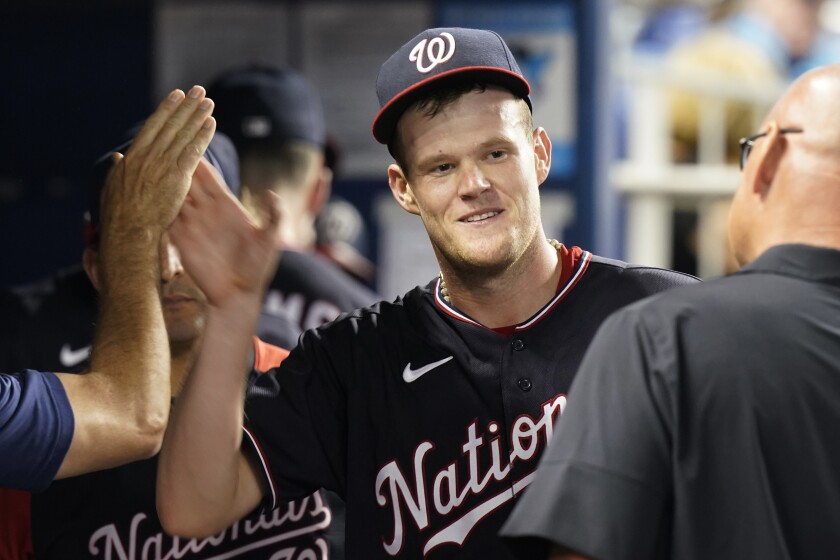 Washington Nationals' pitcher Josh Rogers is congratulated by his teammates after pitching eight inning of a baseball game against the Miami Marlins, Tuesday, Sept. 21, 2021, in Miami. The Nationals defeated the Marlins 7-1. (AP Photo/Marta Lavandier)