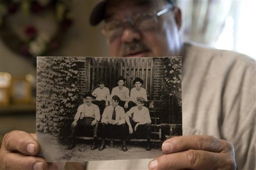 In this Sept. 4, 2009 photo taken in Honea Path, S.C., James D. Cannon holds a family photo that shows his grandfather, Claude Cannon, seated in the front row far left, who was killed in the Chiquola Mill shooting in 1934 where seven people died and more than 34 people injured over labor unions that the mill didn't want. (AP Photo/Mary Ann Chastain)