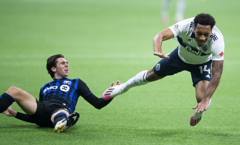 Vancouver Whitecaps forward Theo Bair and Montreal Impact defender Luis Binks fall during the second half of an MLS soccer match Wednesday, Sept. 16, 2020, in Vancouver, British Columbia. (Jonathan Hayward/The Canadian Press via AP)