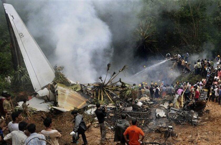 FILE - In this May 22, 2010 file photo, civilians look on as Indian firefighters and rescue personnel try to extinguish the fire around the site of an Air India plane that crashed in Mangalore, in the southern Indian state of Karnataka. From 2011-2030, Boeing and Airbus both predict Asia will account for about a third of global aircraft deliveries worth a total of more than $1 trillion. To keep up with growth and replace retiring pilots, Boeing forecasts Asia-Pacific will need 182,300 new pilots over the next 20 years, with about two-fifths of that demand coming from China. (AP Photo/File)