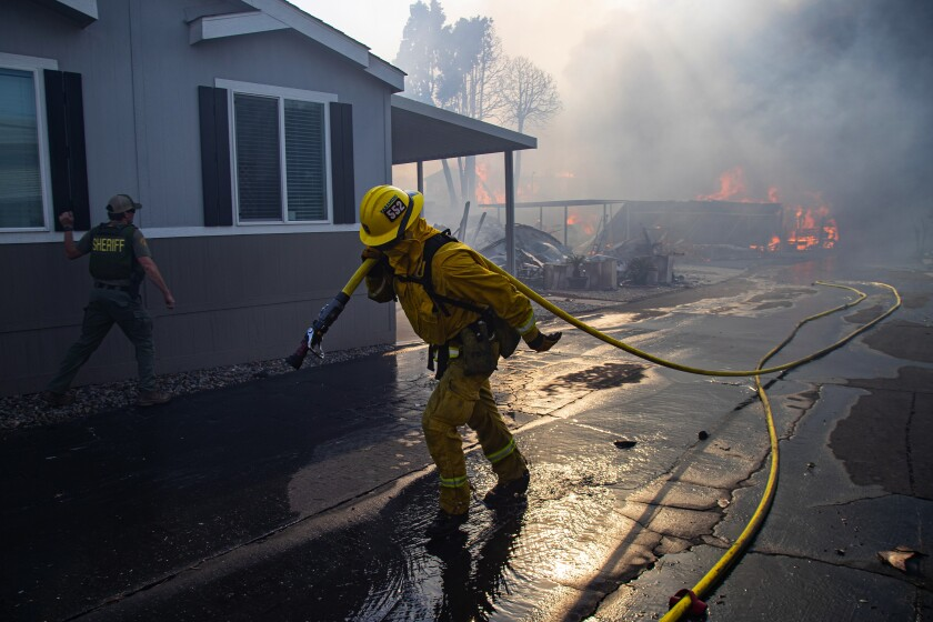 A firefighter hauls a hose in the Villa Calimesa Mobile Home Park, where the Sandalwood fire destroyed 74 homes and buildings.