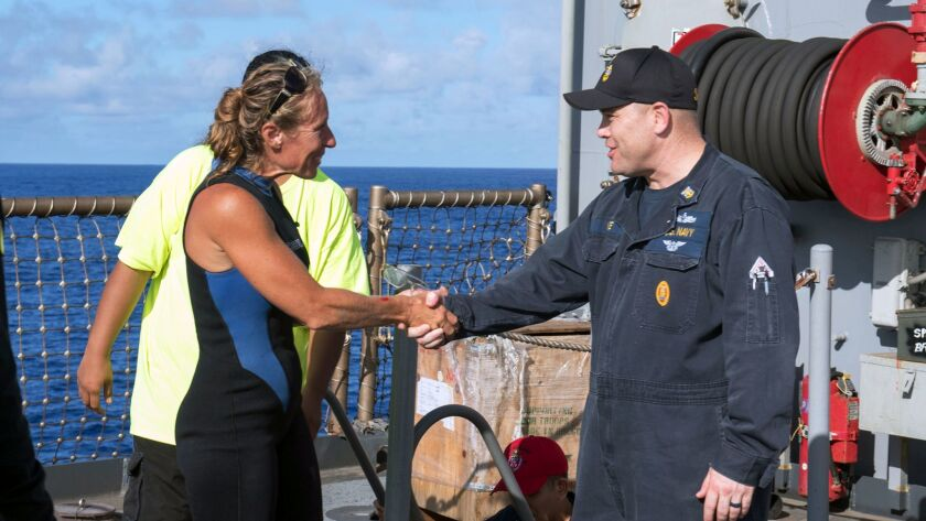 USS Ashland Command Master Chief Gary Wise welcomes aboard Jennifer Appel, one of two Honolulu women and their dogs who were rescued after being lost at sea.