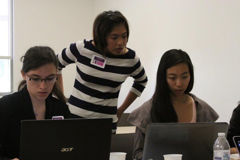 Sandra Lamantas (center) works with teammates Audrey Fonseca (left) and Julia Yang (right) at the 2014 International Women's Hackathon at Cal State San Marcos Saturday.