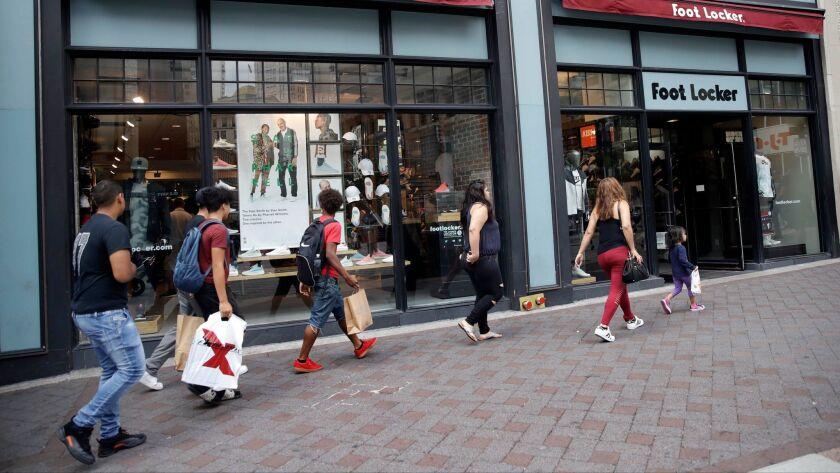 Shoppers walk past a Foot Locker store in Boston on Aug. 25.