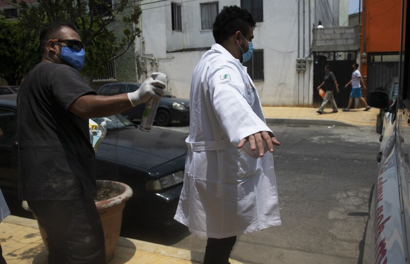 A health worker disinfects a fellow colleague after outside the home of a 75-year-old resident who they tested for COVID-19, in Mexico City, Wednesday, June 17, 2020. (AP Photo/Marco Ugarte)
