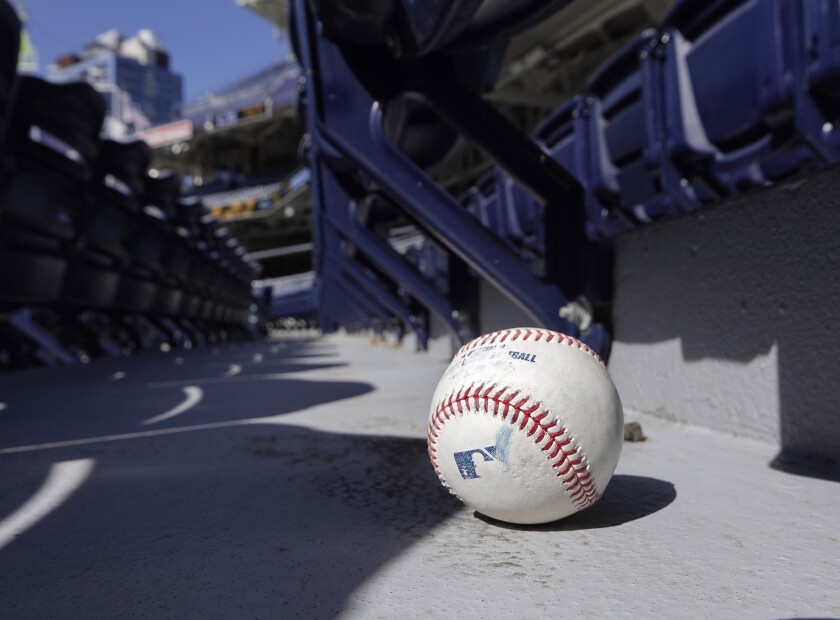 A foul ball from Padres batting practice sits in the stands at a summer camp practice at Petco Park.