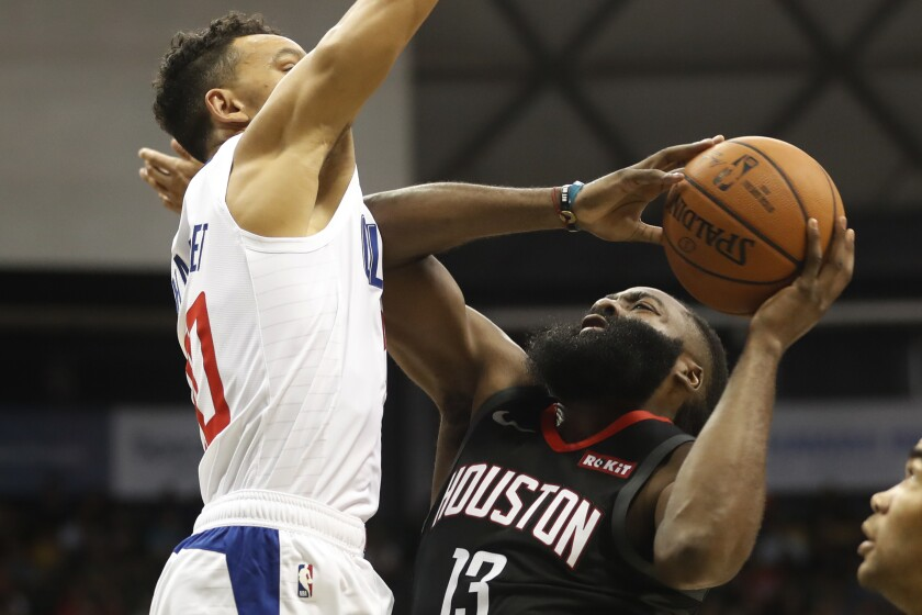 Houston Rockets shooting guard James Harden (13) shoots over Los Angeles Clippers point guard Landry Shamet (20) during the first quarter of an NBA preseason basketball game, Thursday, Oct 3, 2019, in Honolulu. (AP Photo/Marco Garcia)