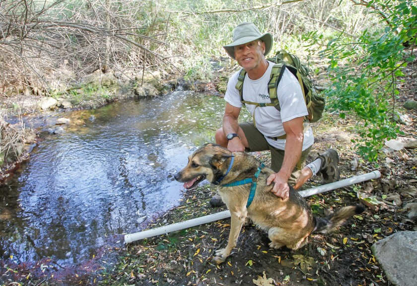 Lance Cummings, 57, of Cardiff hikes with his dog, Buddy, on Thursday in San Elijo Hills area of San Marcos. He's in training for a Spartan-inspired rucking (hiking with a weighted pack) trip across Greece in May that will cover 250 miles in eight days.