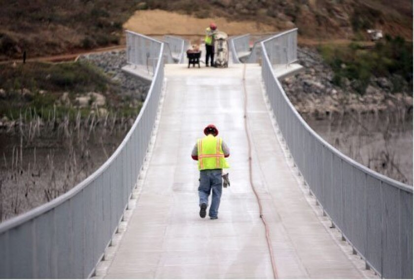 Construction crews Tuesday worked on the concrete surface of the bridge over Lake Hodges. Despite signs saying the span  is closed, pedestrians and bicyclists have used the bridge.