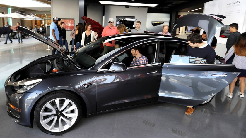 People check out the Tesla Model 3, which starts at $35,000 before incentives; it's the most afforda