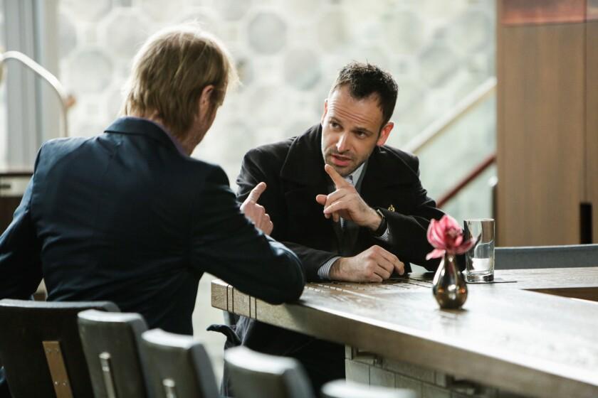 "Rhys Ifans, left, as Mycroft Holmes and Jonny Lee Miller as Sherlock Holmes in ""Elementary."""