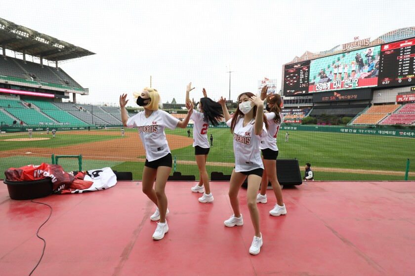 Cheerleaders dance on top of a dugout at Happy Dream Ballpark during a spectator-free KBO game between SK Wyverns and Hanwha Eagles on May 5 in Incheon, South Korea.