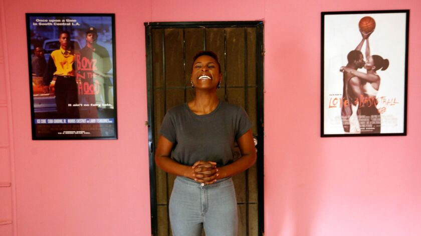 """Actress Issa Rae enjoys a light moment between the movie posters for, """"Boyz N the Hood,"""" and """"Love and Basketball,"""" at her office in Inglewood."""