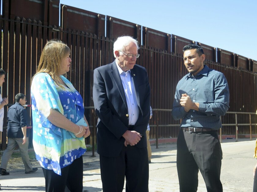 Democratic presidential candidate Bernie Sanders and his wife Jane speak with a young immigrant named Julio Zuniga who told him about his struggles in this country after being brought here illegally by his family, after a Sanders news conference near the U.S.-Mexico international border in Nogales, Ariz., Saturday, March 19, 2016. He focused on immigration and said he would fight for immigration reform. (AP Photo/Astrid Galvan)