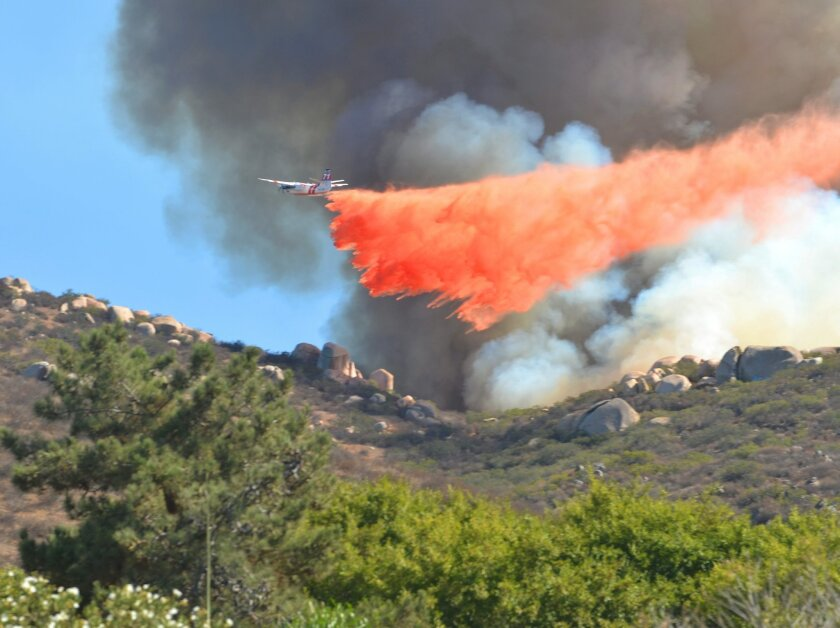 A Cal Fire firefighting aircraft drops fire retardant on a brush fire that started in Lakeside on Aquilla Drive near El Nopal, not far from Santee.