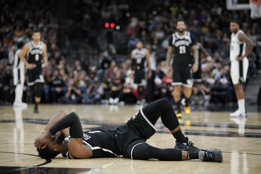 Brooklyn Nets' David Nwaba lies injured on the court during the second half of the team's NBA basketball game against the San Antonio Spurs, Thursday, Dec. 19, 2019, in San Antonio. San Antonio won 118-105. (AP Photo/Darren Abate)