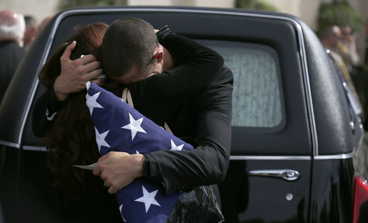 Branden Owen, right, hugs his mother Jennifer outside his father Steve Owen's hearse after the memorial service at Lancaster Baptist Church in Lancaster.