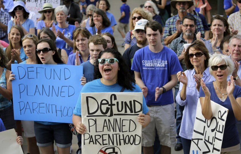 FILE- In this July 28, 2015 file photo, Erica Canaut, center, cheers as she and other anti-abortion activists rally on the steps of the Texas Capitol in Austin, Texas to condemn the use in medical research of tissue samples obtained from aborted fetuses. Two state health researchers in Texas are un