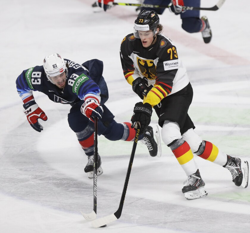 Conor Garland of the US, left, challenges for the puck with Germany's Lukas Reichel during the Ice Hockey World Championship group B match between United States and Germany at the Arena in Riga, Latvia, Monday, May 31, 2021. (AP Photo/Sergei Grits)