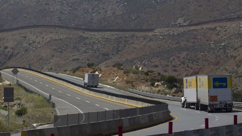 Traffic moves along Baja California's Highway 2 toll road between Otay and Tecate.  The international border fence is visible in the background.