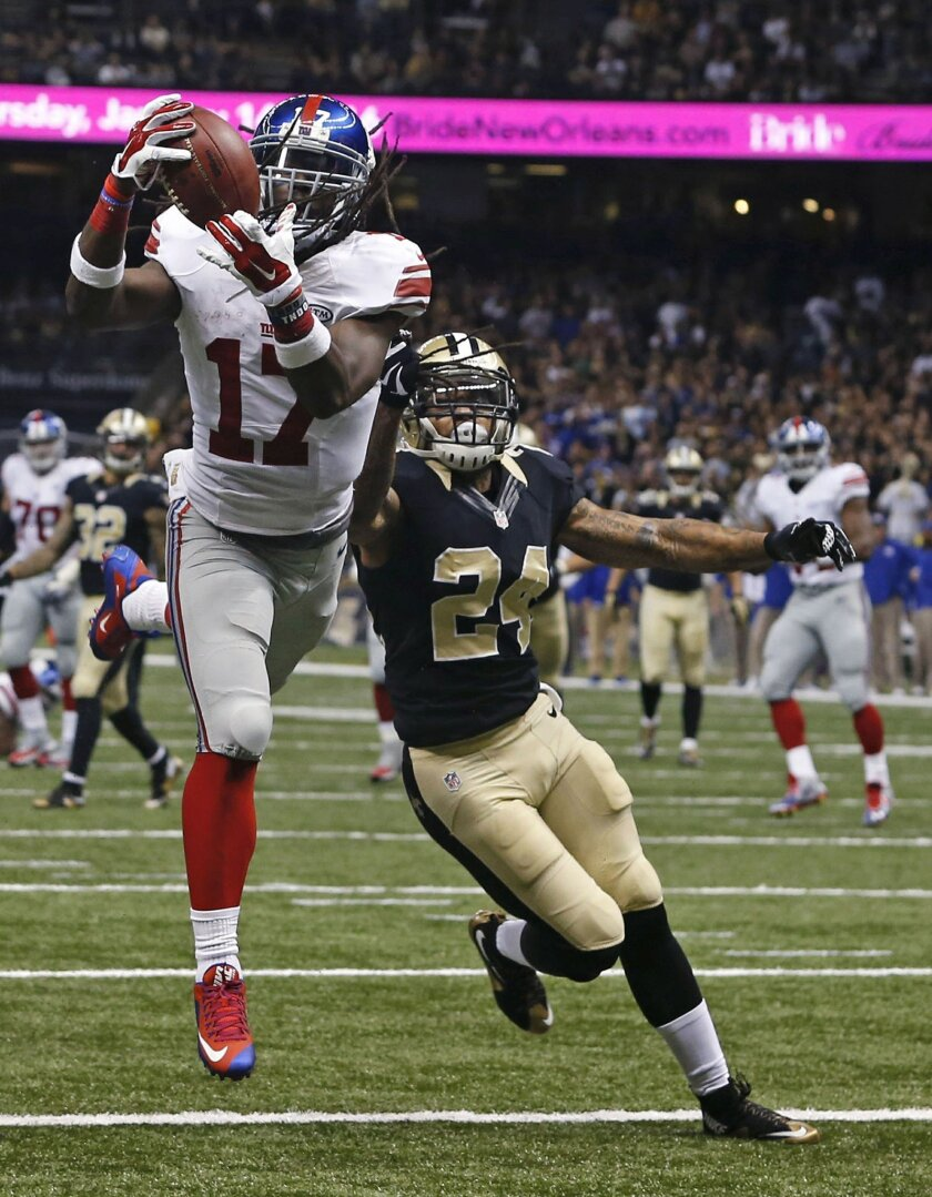 New York Giants wide receiver Dwayne Harris (17) pulls in a touchdown reception in front of New Orleans Saints defensive back Kyle Wilson (24) in the second half of an NFL football game against the New Orleans Saints in New Orleans, Sunday, Nov. 1, 2015. (AP Photo/Jonathan Bachman)