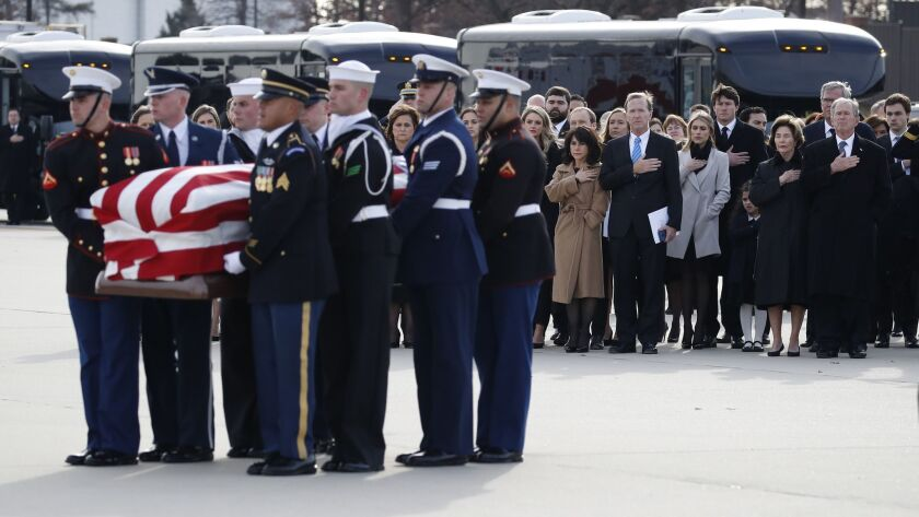 The Bush family watches as the flag-draped casket of former President George H.W. Bush is carried by a military honor guard.