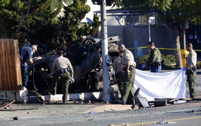Investigators survey vehicle that crashed following a high-speed pursuit by sheriff's deputies. (Irfan Khan/Los Angeles Times.)