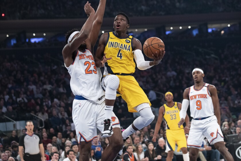 FILER - In this Feb. 21, 2020, file photo, Indiana Pacers guard Victor Oladipo (4) goes to the basket against New York Knicks center Mitchell Robinson (23) in the first half of an NBA basketball game at Madison Square Garden in New York. The Pacers will finish this season without Oladipo after the two-time All-Star decided to sit out because of the risk of re-injuring his right knee. (AP Photo/Mary Altaffer)