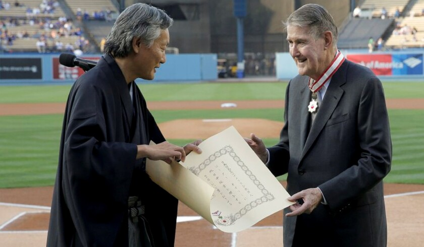 Former Dodgers President Peter O'Malley, right, receives the Order of the Rising Sun from the consul general of Japan in Los Angeles, Harry H. Horinouchi, as part of Japan Night at Dodger Stadium.