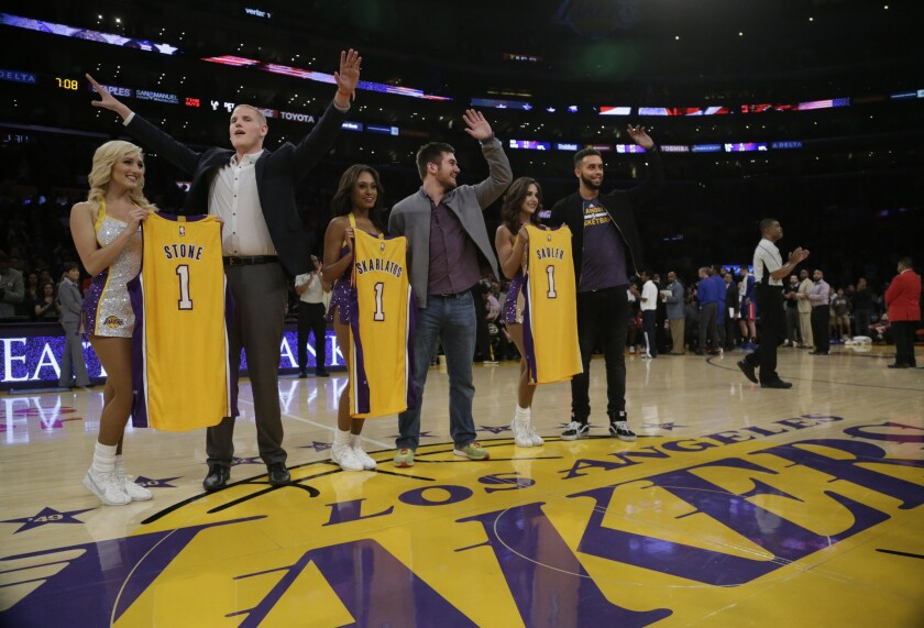 The Laker Girls present jerseys to Spencer Stone, Alek Skarlatos and Anthony Sadler during a game against the Pistons. The three American men foiled a terrorist attack on a Paris-bound train in August.