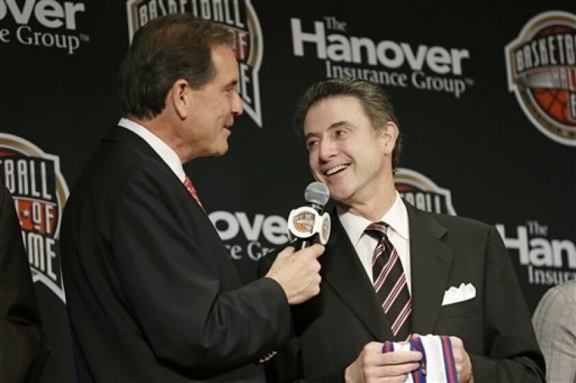 Louisville coach Rick Pitino talks with CBS announcer Jim Nantz, left, during the Naismith Memorial Basketball Hall of Fame class announcement, Monday, April 8, 2013, in Atlanta, Georgia. (AP Photo/Charlie Neibergall)