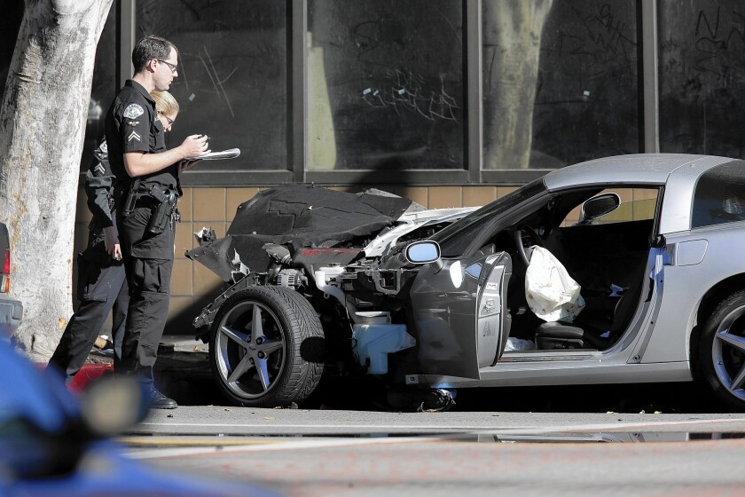 Officers investigate the scene of the LAPD's fatal shooting of an unarmed driver who crashed his car downtown after a high-speed chase.