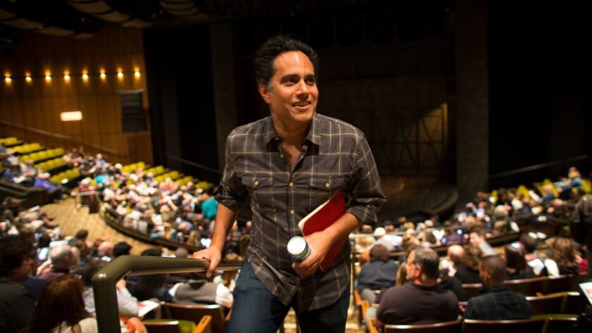 """Playwright Rajiv Joseph walks to his seat for the world premiere of his new play, """"Archduke,"""" at the Mark Taper Forum in Los Angeles."""