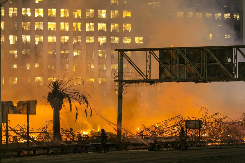 Los Angeles firefighters battle the blaze at the Da Vinci apartments in downtown Los Angeles in January. The developer behind the complex addressed criticisms of the buildings in a new interview.