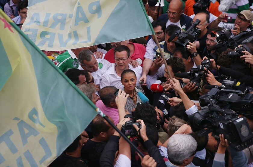 Marina Silva, surrounded by journalists, greets a supporter in the Rocinha favela in Rio de Janeiro Aug. 30, 2014.